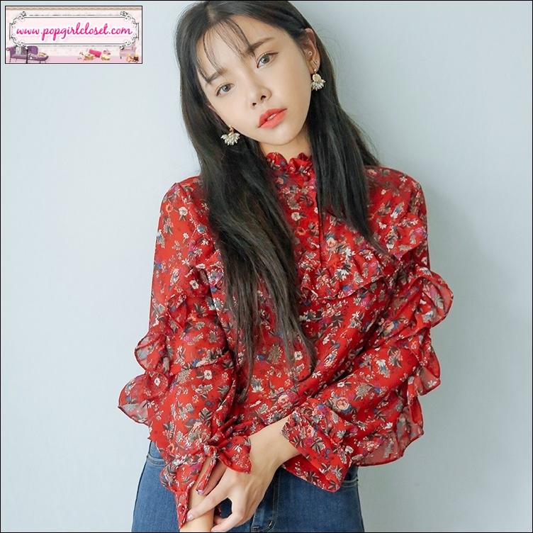 เสื้อชีฟองซีทรูสีแดงลายดอก ดีไซน์วินเทจคอปิดมีกระดุมช่วงอก ดีเทลมีระบายช่วงอก หลัง และช่วงแขน ให้ลุคเกิร์ลลี่
